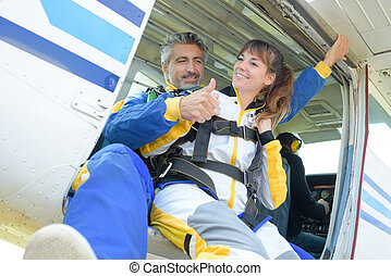 Man and lady poised to do a tandem skydive