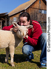 Man and lamb and a farmhouse