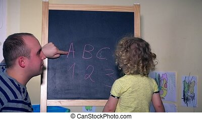 Man and little girl child learning numbers and letters on chalk black board