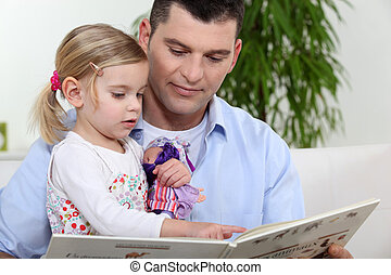 Man and little girl reading a book