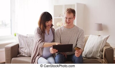 man and pregnant wife shopping online at home - online...