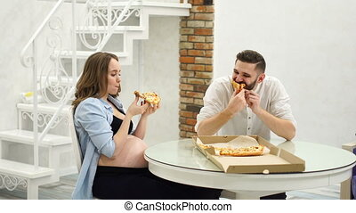 Man and pregnant woman eating pizza at home in their kitchen. A high fat meal, hungry
