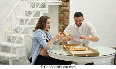 Man and pregnant woman eating pizza at home in their kitchen. Fatty foods