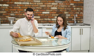 Man and pregnant woman eating pizza at home in their kitchen. Man talking on the phone during dinner