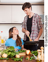man and pretty girl cooking together
