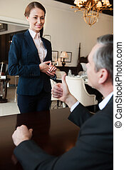 Man and sales clerk. Confident mature man in formalwear gesturing while communicating with sales clerk