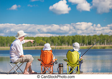 man and sons sit on the pier and fishing