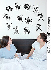 Man and surprised woman in bedroom surrounded looking up at horo