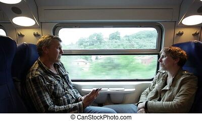 man and the woman go by the train sitting the friend opposite to the friend and talk