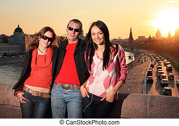 Man and two beautiful young women in Moscow city at sunset....