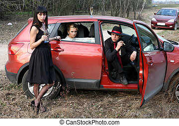 man and two woman with cigar, wine in car