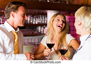 Man and two women in hotel bar - Man and two women in a ...