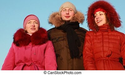 Man and two women in jacket talking outdoors at winter
