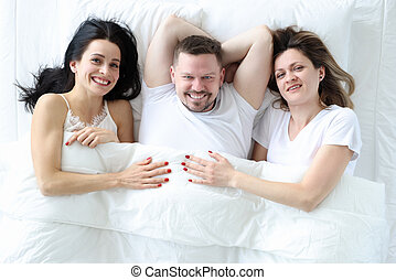 Man and two women lying in bed top view. Promiscuous sex concept