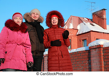 man and two women standing on outdoors in winter near to house, friends smiling