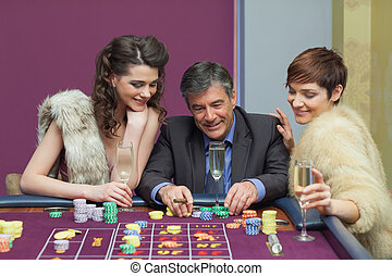 Man and two women talking at roulette table