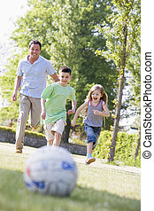 Man and two young children outdoors playing soccer and having fu