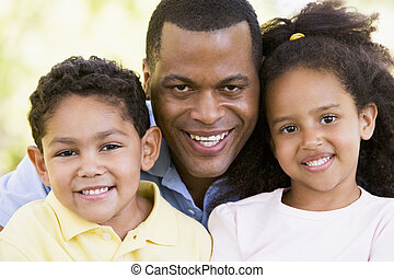 Man and two young children outdoors smiling