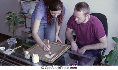 Man and woman are applied primer on canvas