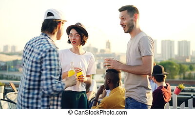 Man and woman are chatting at open-air party then greeting...