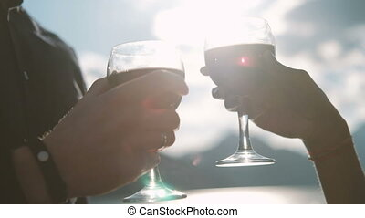 Man and woman are drinking wine in glasses against the blue sky.