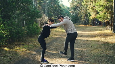 Man and woman are enjoying sports in park holding each other's shoulders and moving legs warming-up joints standing on path with green trees around them.