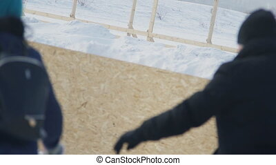 Man and woman as couple skating in rink outdoor in winter.