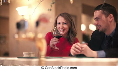 Man and woman at the bar counter. Smiling woman drinking...