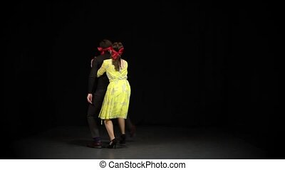 Man and woman behind him walk around the studio blindfolded. Relationship concept, people are nearby and do not see each other. Slow motion