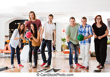 Man And Woman Bowling With Friends in Club