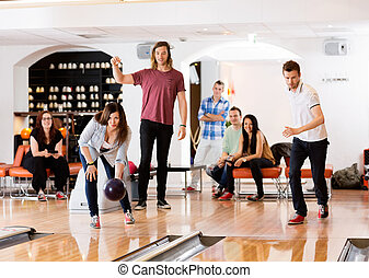 Man And Woman Bowling With Friends in Background - Young man...