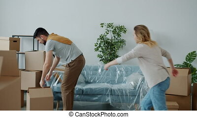 Man and woman are bringing boxes to new house then having fun together enjoying relocation laughing in beautiful modern room. Youth and housing concept.