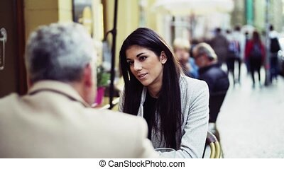 Man and woman business partners sitting in a cafe in city,...
