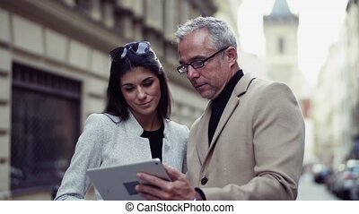 Man and woman business partners standing outdoors in city,...