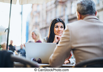 Man and woman business partners with laptop sitting in a cafe in city, talking.