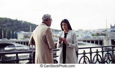 Man and woman business partners with smartphone standing by...