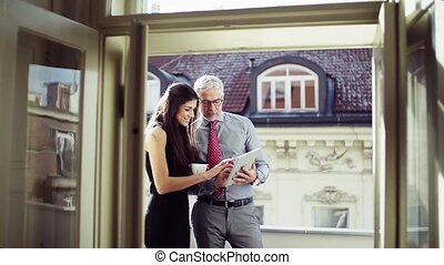 Man and woman business partners with tablet standing on a...