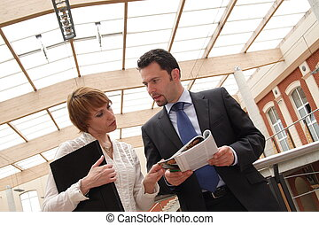 Business man and woman conversing, standing in a courtyard.