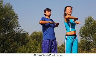 man and woman carries out exercises in park together