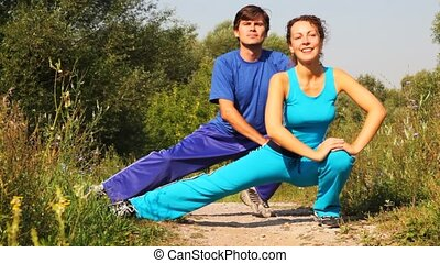 man and woman carries out exercises on path in park together