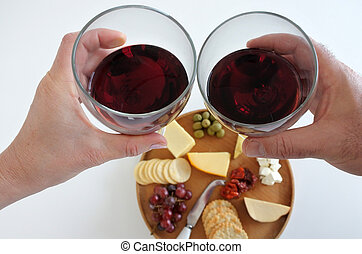 Man and woman cheering with wine over a cheese platter