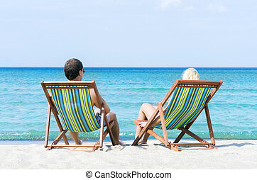 Man and woman chilling on a summer beach