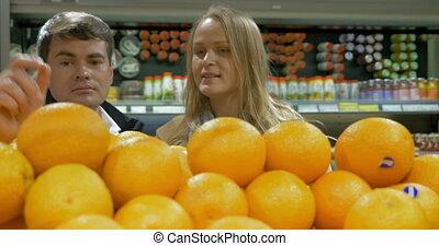 Man and woman choosing oranges