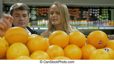Man and woman choosing oranges