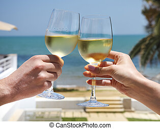 Man and woman clanging wine glasses with white wine at sky...