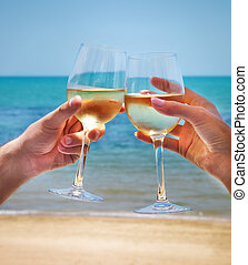 Man and woman clanging wine glasses with white wine at sea backg
