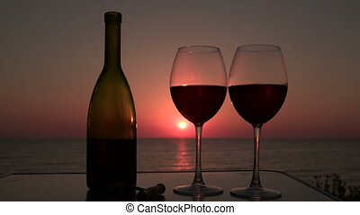 Man and woman clinked glasses with red wine at sunset