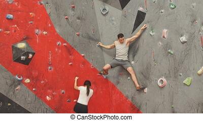 Man and woman competing at rock climbing wall. - Sporty man...