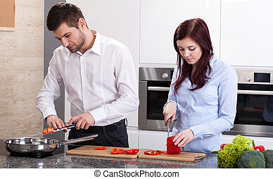 Man and woman cooking dinner