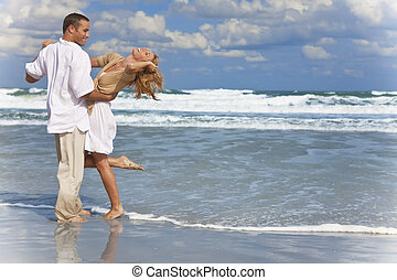 A young man and woman having fun dancing as a romantic couple on a beach with a bright blue sky